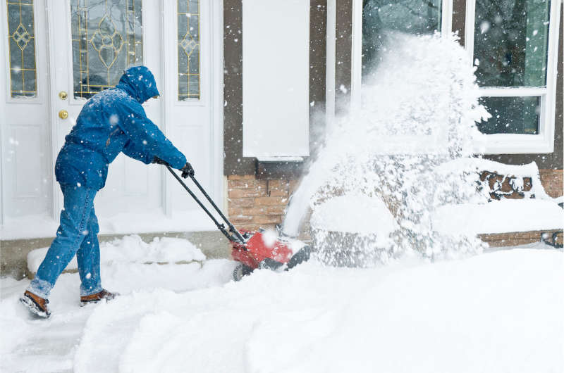 professional removing snow from in front of a house