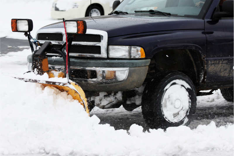 Plowing away snow using a heavy duty snow removal truck